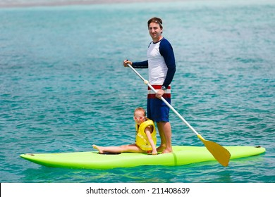 Father and his adorable little daughter paddling on stand up board having fun during summer beach vacation
