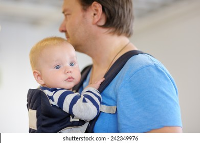 Father and his baby boy in a baby carrier