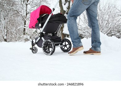 A Father with his Baby in a buggy on a snowy track