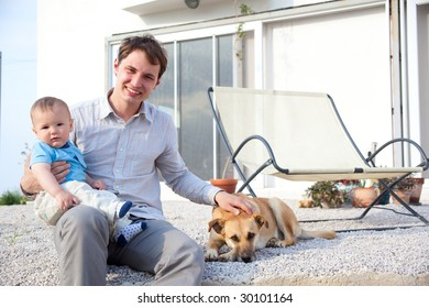 father with his baby son and dog in front of a house