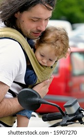 father and his baby-boy in sling carrier look at motorbike