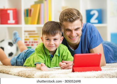 father and his child son play with tablet pc