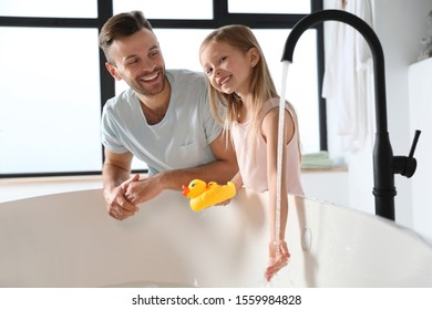Father with his cute little daughter filling tub in bathroom