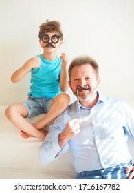 Father and his cute little son put on paper beard and smile