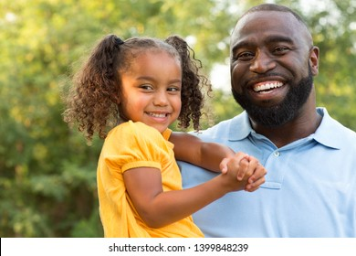 Father and his daughter laughing and playing outside.