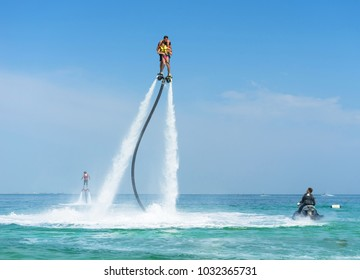Father and his daughter posing at new flyboard at tropical beach. Positive human emotions, feelings, joy. Funny cute child making vacations and enjoying summer.