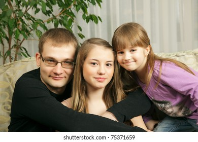 Father with his daughters sitting on sofa together