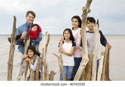 Father with his five children standing by lake shore near driftwood fencing in summer