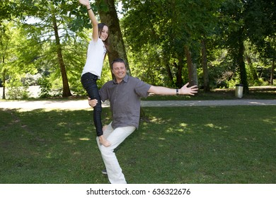 The father and his girl make acrobatics in the park