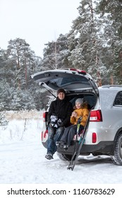 Father and his kid talk together after sports activities such as ski and ice skates. Sitting back trunk of suv at winter season