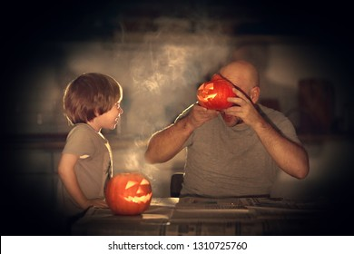 Father and his little cute son are carving halloween pumpkins in the evening. Image with selective focus, noise effect and toning.