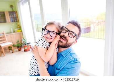 Father with his little daughter in black hipster eyeglasses