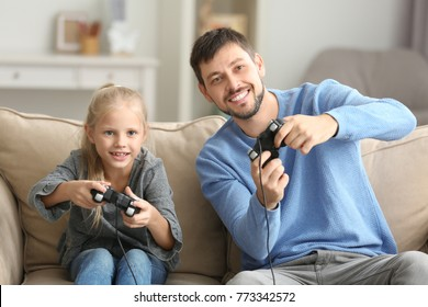 Father and his little daughter playing videogame at home