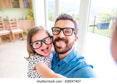 Father with his little daughter sticking tongue out