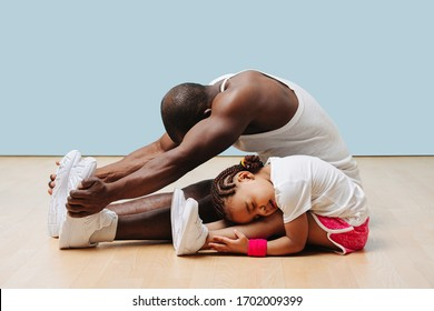 Father and his little daughter stretching knees and backs on the floor at home, folding themselves. Pained faces, feeling tension in ligaments and sinews.