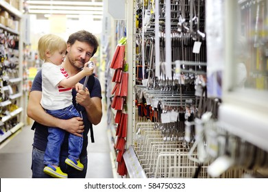 Father and his little son choosing the right tool in a hardware store. Fatherhood concept