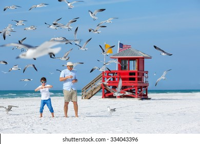 Father and his little son feeding seagulls on tropical beach, Florida summer holiday vacation