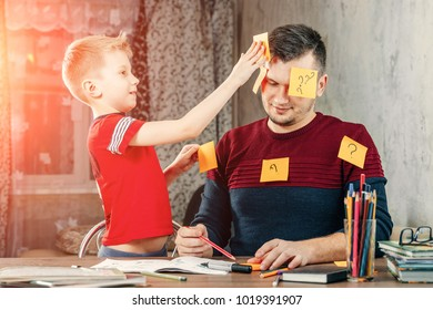 The father and his little son fool around doing homework
