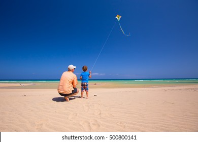 Father and his little son playing with a kite on the beach.