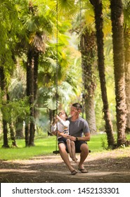 A father and his little son ride on a swing. Wooden swings on long chains hang among palm trees and trees. Family on vacation