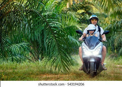 Father and his little son riding motorbike on tropical jungle road with palm trees during island vacation in Asia