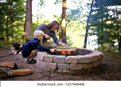 A father and his little son are starting a campfire in a fire ring at a campground overlooking a lake in the woods, as their senior dog lays nearby.