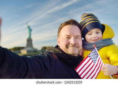 Father and his little son take selfie on the background of the statue of liberty. The concept of family travel