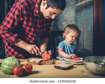 A father and his little toddler are making sandwiches at home
