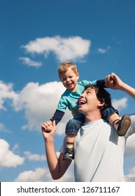 Father and his son against the cloudy sky smiling