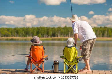 Father with his son and daughter on a wooden pier in the lake fishing with fishing rods