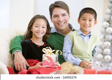 Father And His Son And Daughter Sitting On Sofa,Holding A Christmas Present