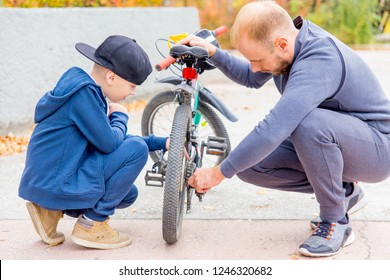 father and his son fixing bike in a park