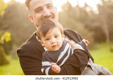 Father with his son in hands in sunny day outside