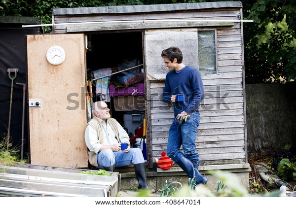 A father and his son having a break on an allotment, drinking tea