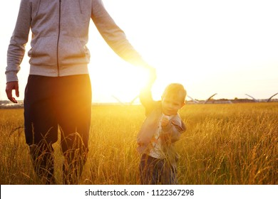 Father with his son holding hands, sunset time