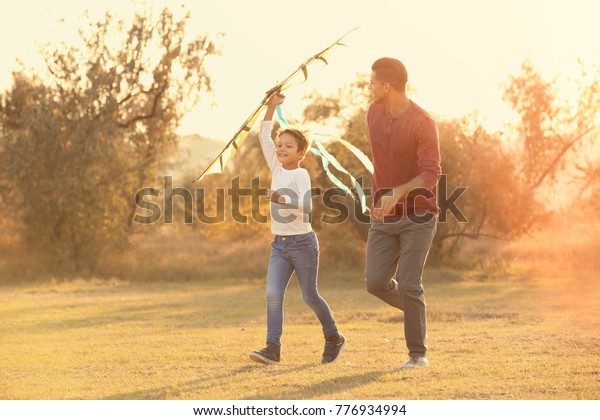 Father and his son with kite in countryside