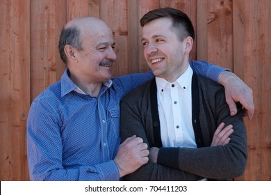 Father and his son looking at each other on wooden background. Good family relationships