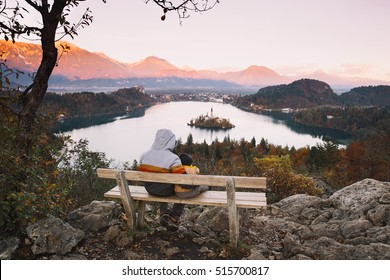 Father and his son looking sunset with amazing view on Bled Lake. Autumn or Winter in Slovenia, Europe. Top view on Island with Catholic Church in Bled Lake with Castle and Mountains in Background.