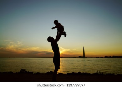 Father with his son on sunset beach, silhouette photo