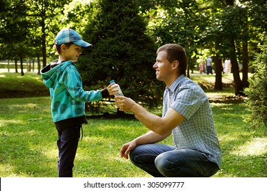 Father with his son in the park .Father is giving water to his boy.