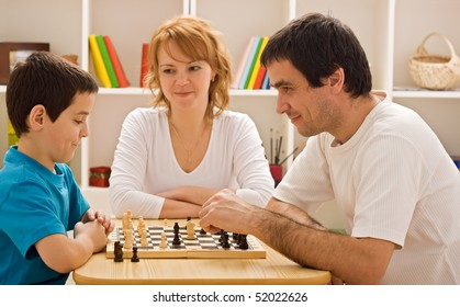 Father and his son playing chess meantime the young beautiful woman smiling