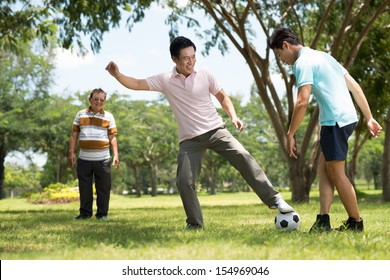Father and his son playing football while the grandfather looking at them on the foreground
