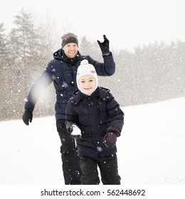 Father and his son playing outside, winter forest on the background, snowing, happy and joyful
