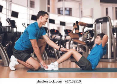 Father with his son in the same clothes in the gym. Father and son spend time together and lead a healthy lifestyle. Boy is pump the abdominals, coach helps him.