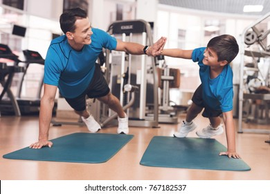 Father with his son in the same clothes in the gym. Father and son spend time together and lead a healthy lifestyle. Dad and son concept. Healthy lifestyle family.