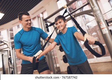 Father with his son in the same clothes in the gym. Father and son spend time together and lead a healthy lifestyle. The boy is engaged in the simulator, the coach helps him.