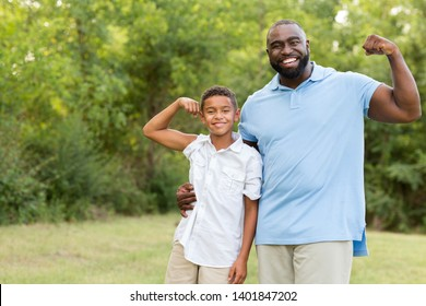 Father and his son smiling and showing their muscles.