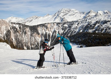 A father with his son are standing on ski piste in high mountains