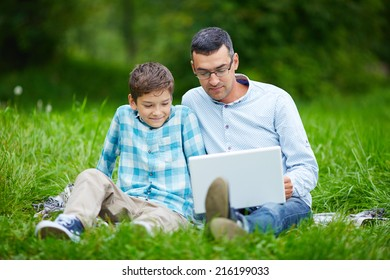 Father and his son using laptop in the park