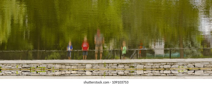 A father with his sons out fishing reflection in the water on the Rideau canal in Ottawa, Canada.